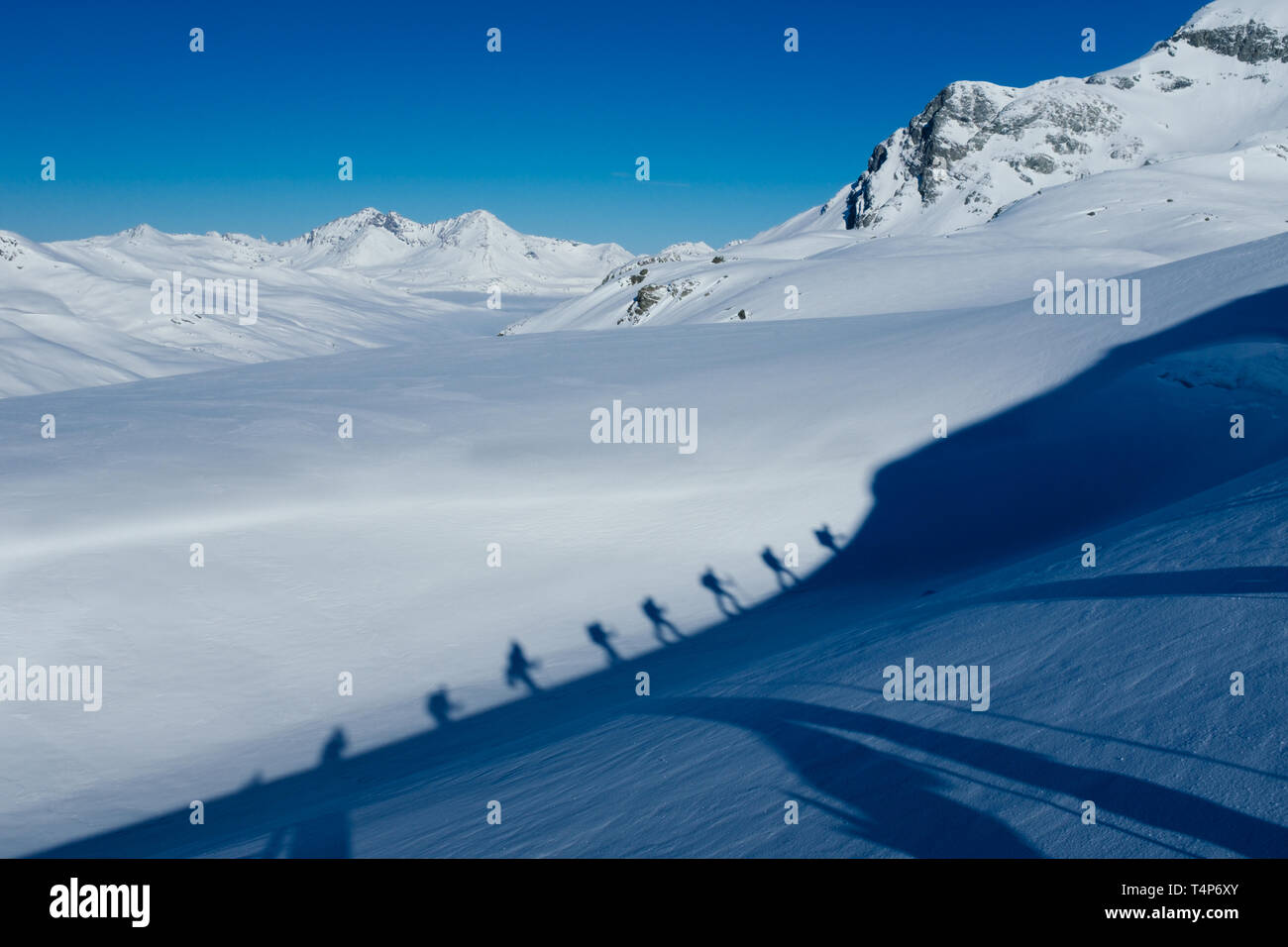Shadows of tour skiers in Switzerland - Stock Image