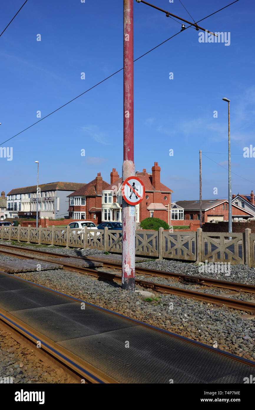 Tramway with no pedestrians warning sign mounted on overhead power lines support pole, light rail track and rubber panels in foreground, Blackpool uk - Stock Image