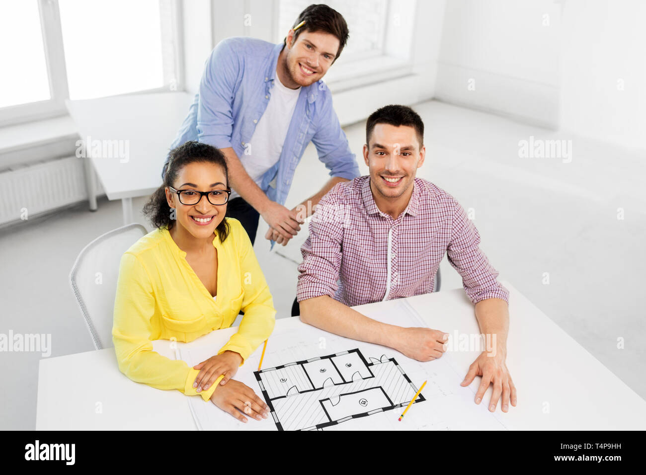 business, architecture and people concept - creative team of architects or interior designers with blueprint working at office Stock Photo