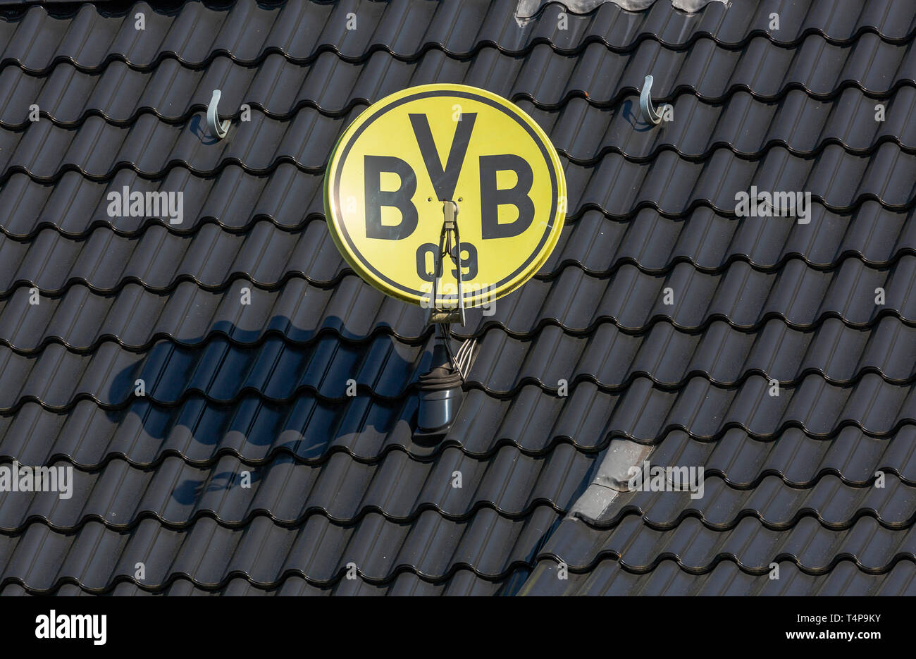 symbolic image, parabolic antenna in club colours and with club emblem of the German football club BVB 09 Borussia Dortmund on a house roof, television aerial, satellite TV, sports, football, Bundesliga, football mania, club loyalty, roofing tiles Stock Photo