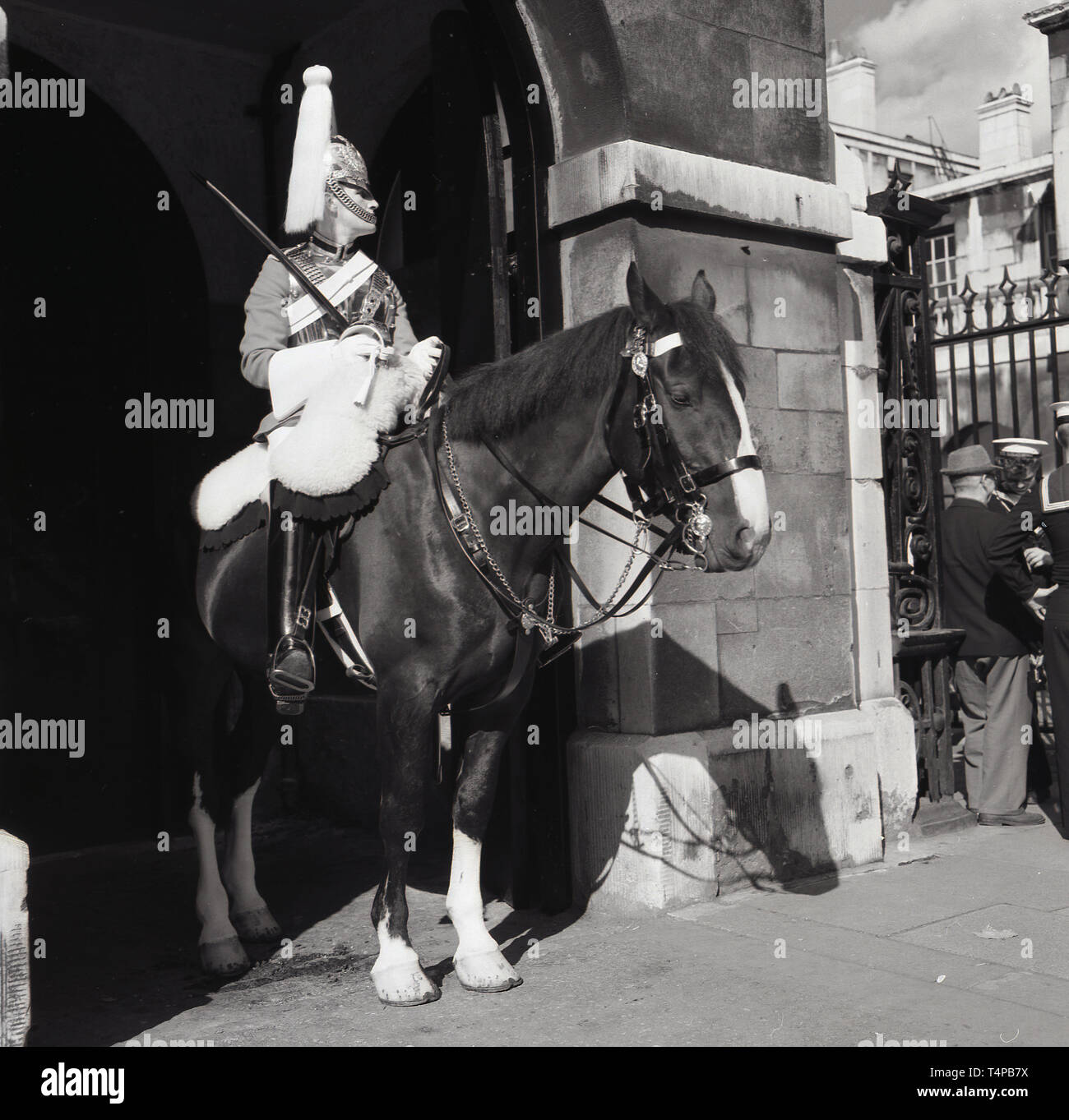 1960s, historical, London, Summer time and a Life Guard of the Household Cavalry mounted reigment in full ceremonial uniform sitting on his horse doing on sentry duty, - Stock Image