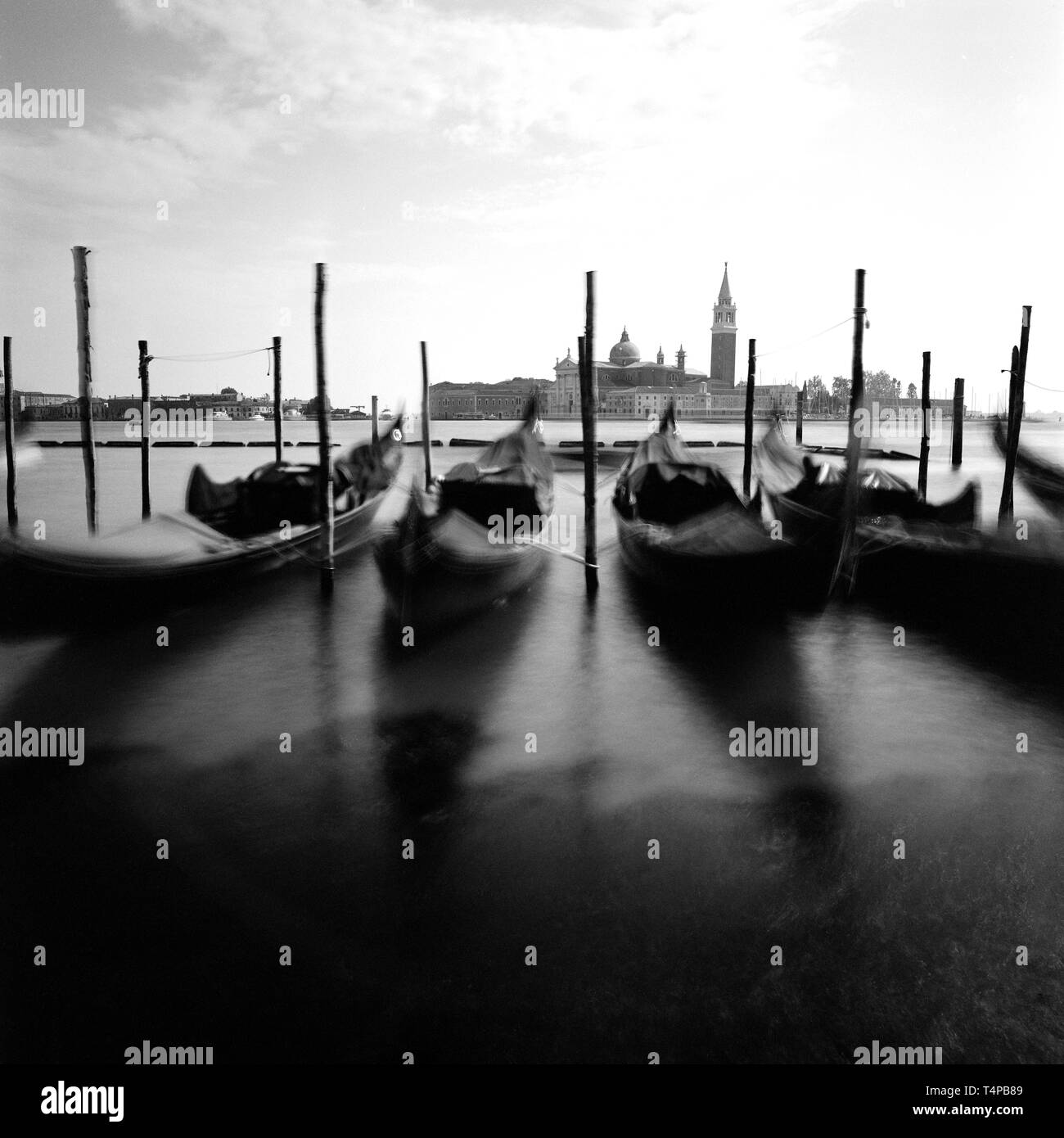 gongolas in Venice Italy. Analog black and white photography. lon exposure artwork. - Stock Image