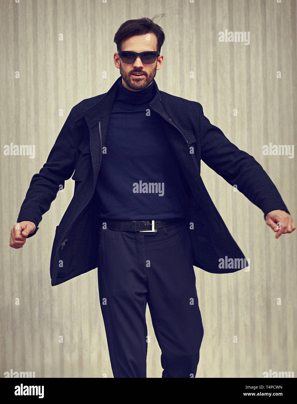 Fashion beard style business handsome male model in fashion sunglasses with serious concentrated look whirling and moving in style clothing on wall ou - Stock Image