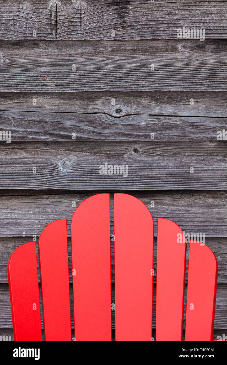 Back support of a Cape Cod chair against weathered cedar siding of a heritage building Stock Photo