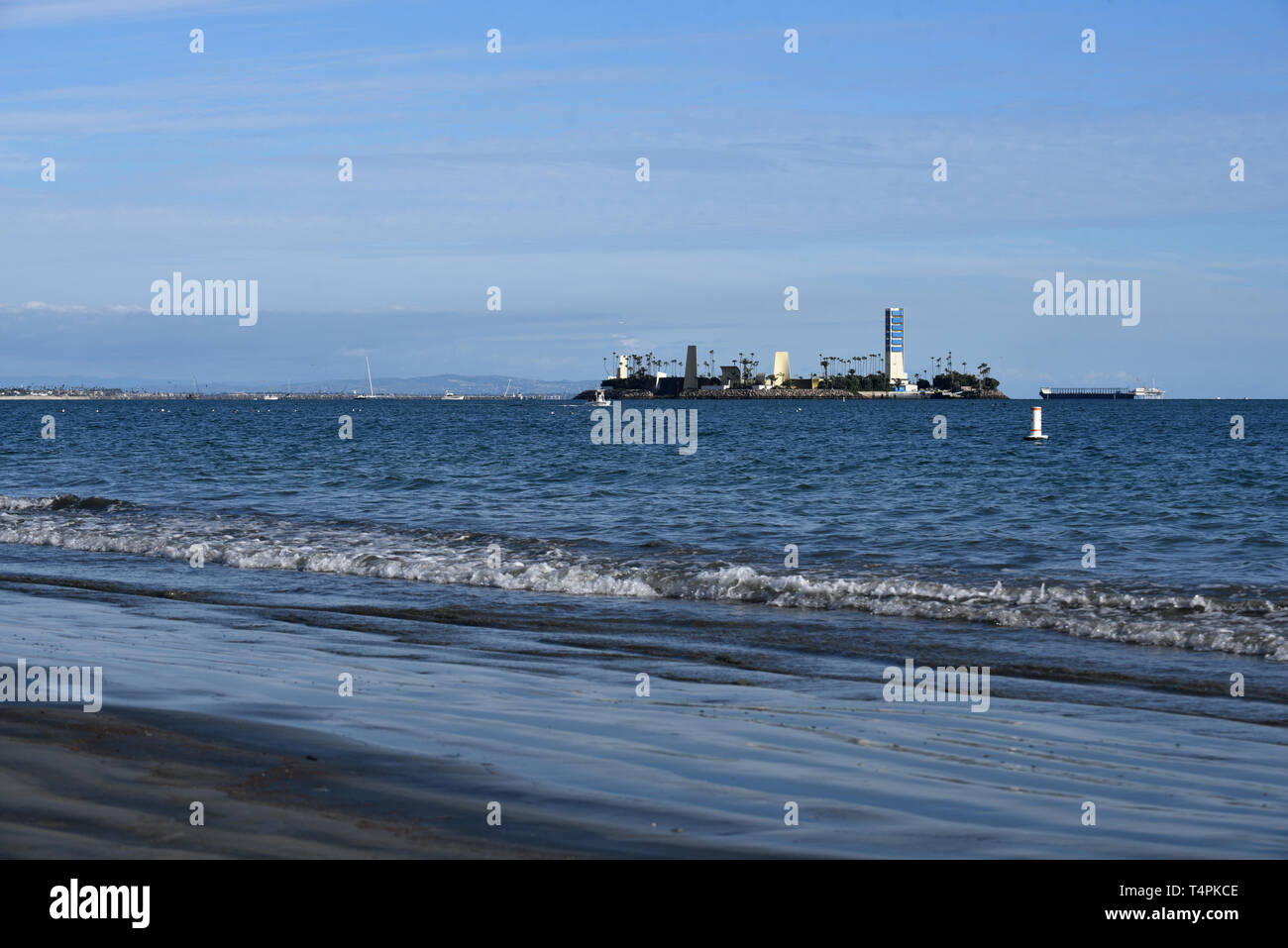 Water coming to shore and the sand is noticably dirty on Alamitos beach from offshore oil drilling - Stock Image
