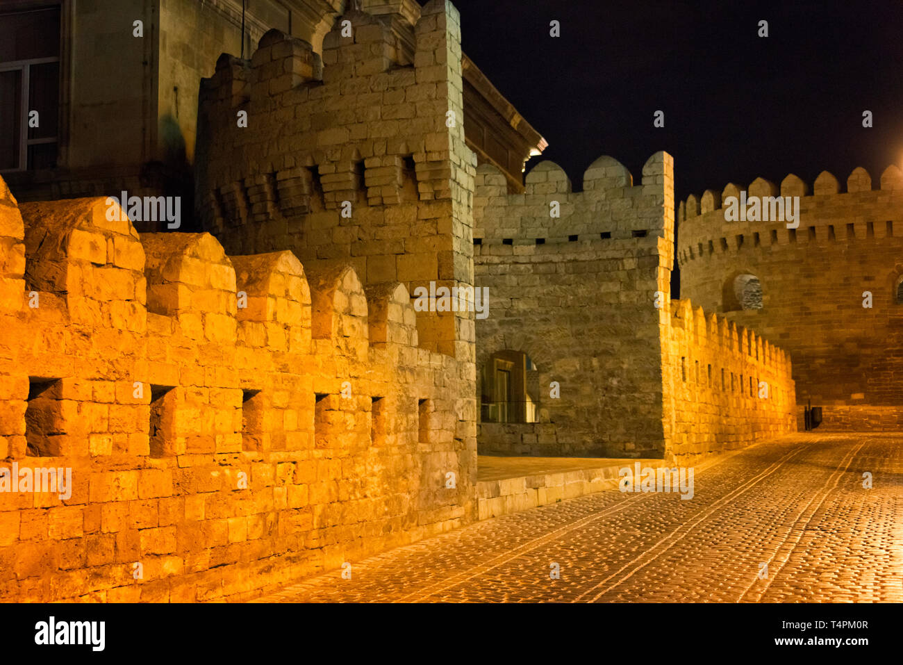 Old city wall and cobblestone street in the Inner City of Baku at night, Azerbaijan - Stock Image