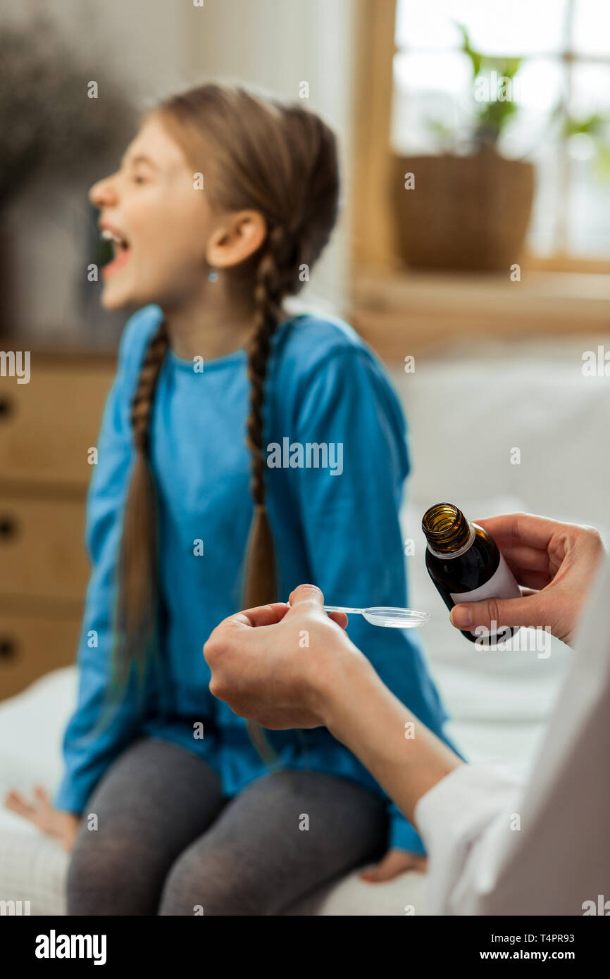 Small mischievous patient. Small sick mischievous patient with long braids wearing blue blouse loudly refusing to take throat syrup offered by a pedia - Stock Image