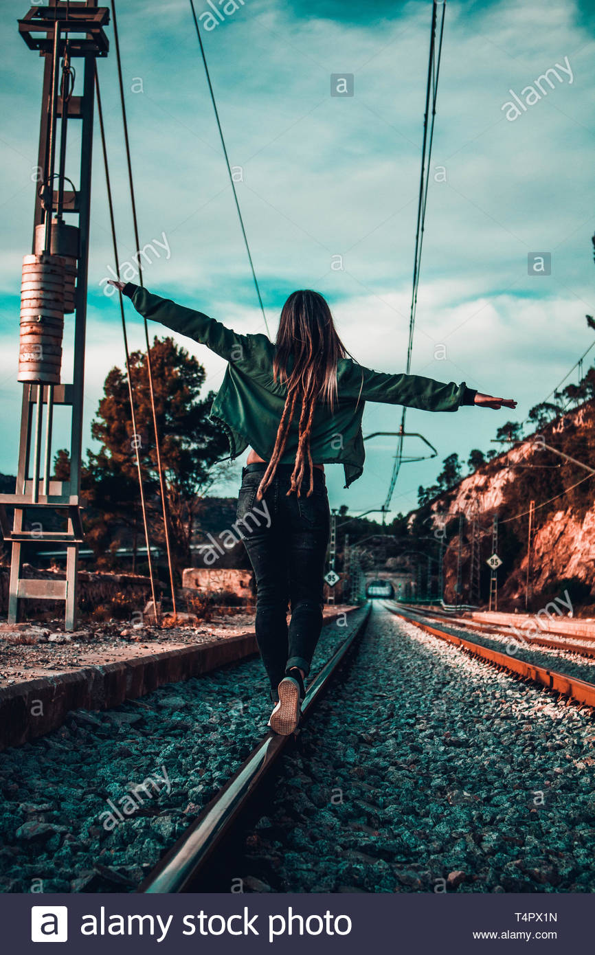 person tip toeing on railroad - Stock Image