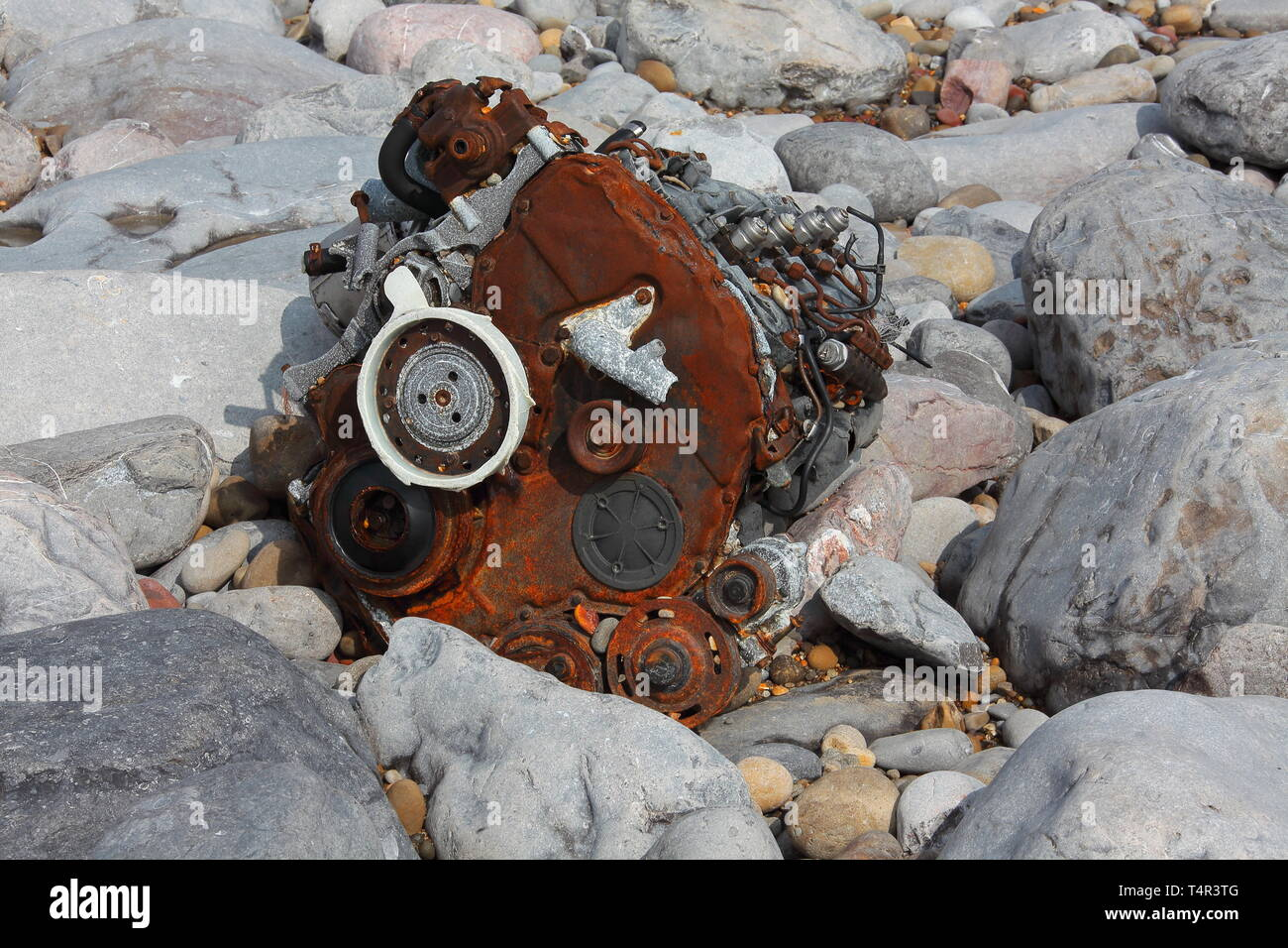 What now remains of a Beach buggy engine and transmission washed back a mile along the shore from its position last year and in a sorry state. - Stock Image
