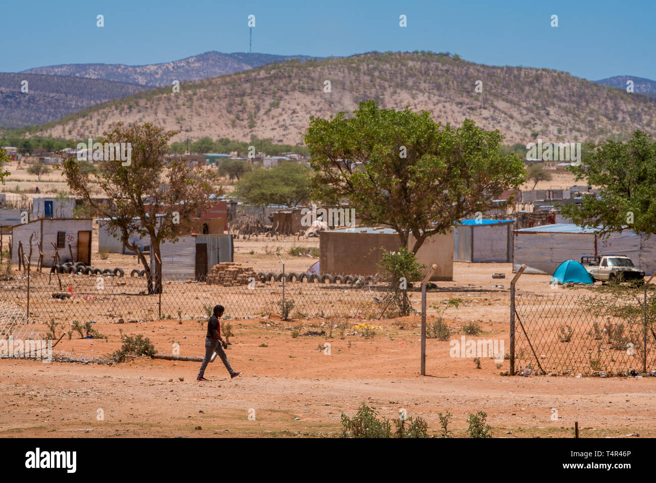 Opuwo/Namibia - November 6 2018: A man walking in the desert village, with shacks and hills in the background - Stock Image