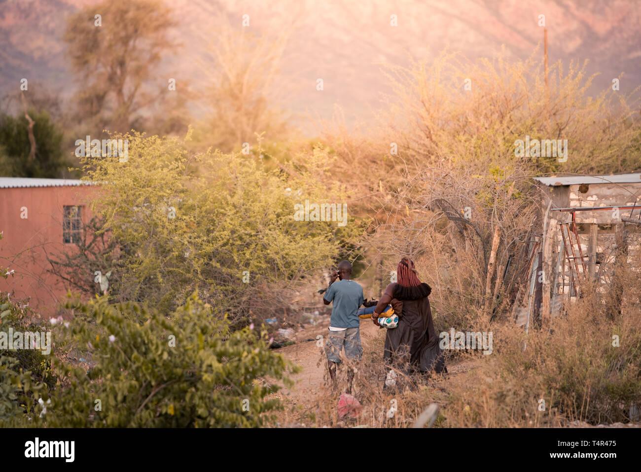 Opuwo/Namibia - November 6 2018: A man and Himba woman walking into the bushes at sunset - Stock Image