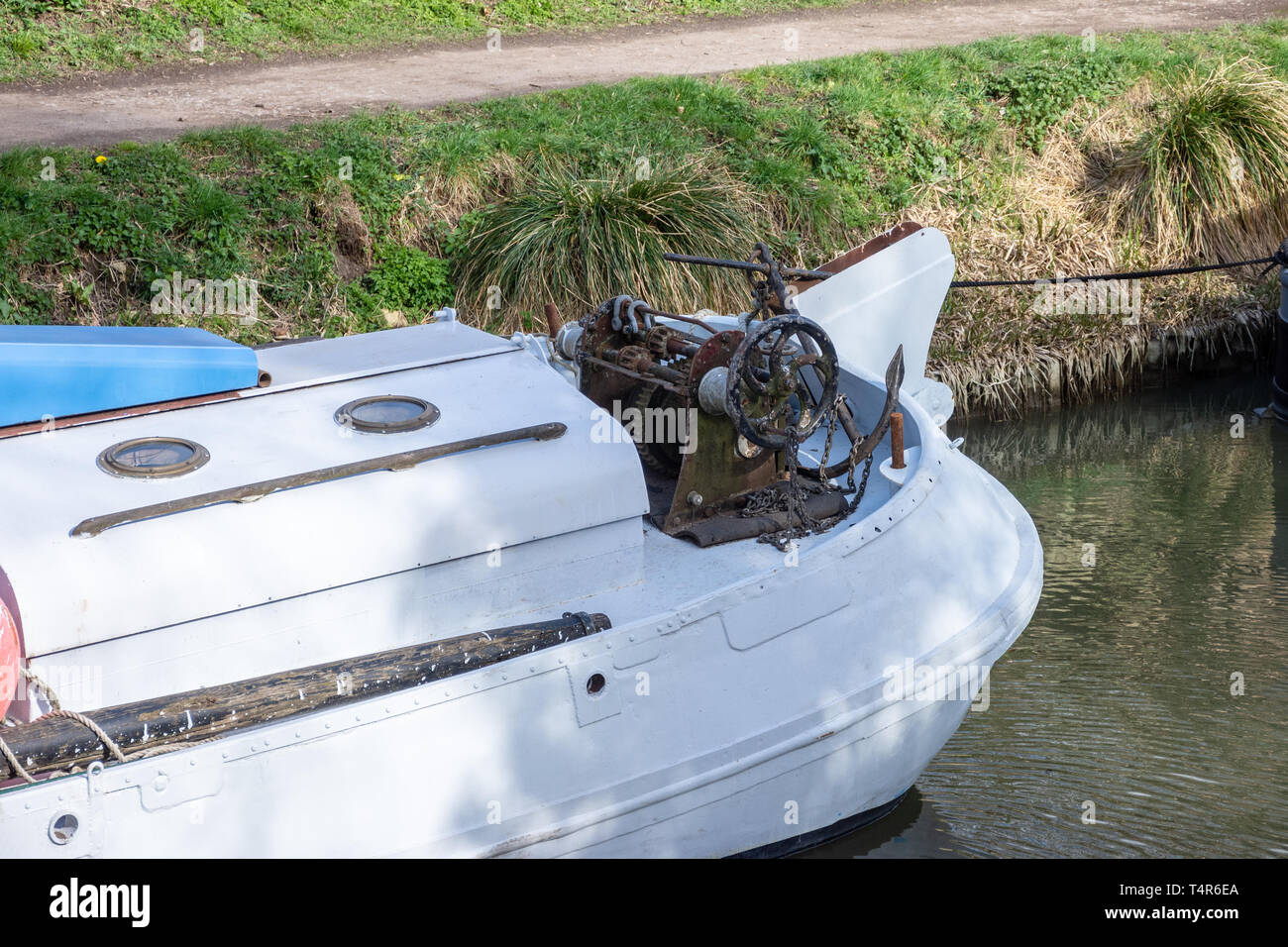 The stern of a river sailing boat with an old vintage rusty hand winch and anchor on the Kennet and Avon canal in Bradford on Avpn Wiltshire. Stock Photo