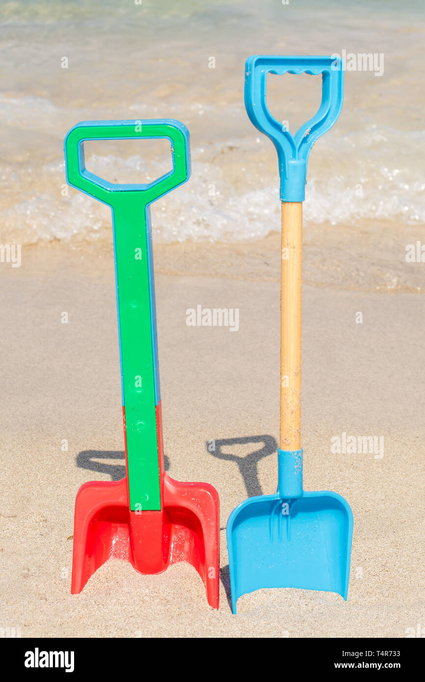 Two shovels stuck on the beach in the sand Stock Photo
