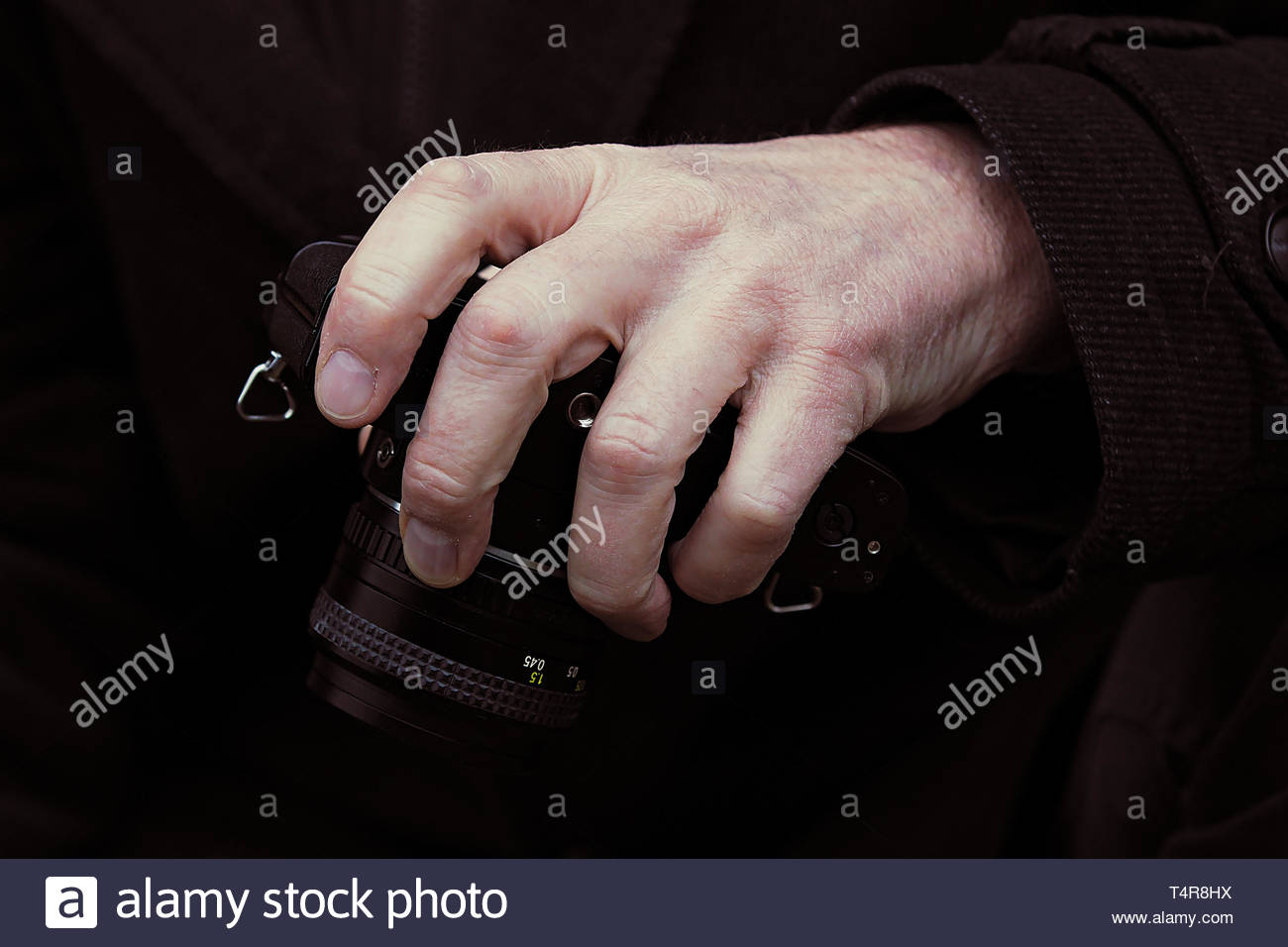 grasping lowered camera - Stock Image
