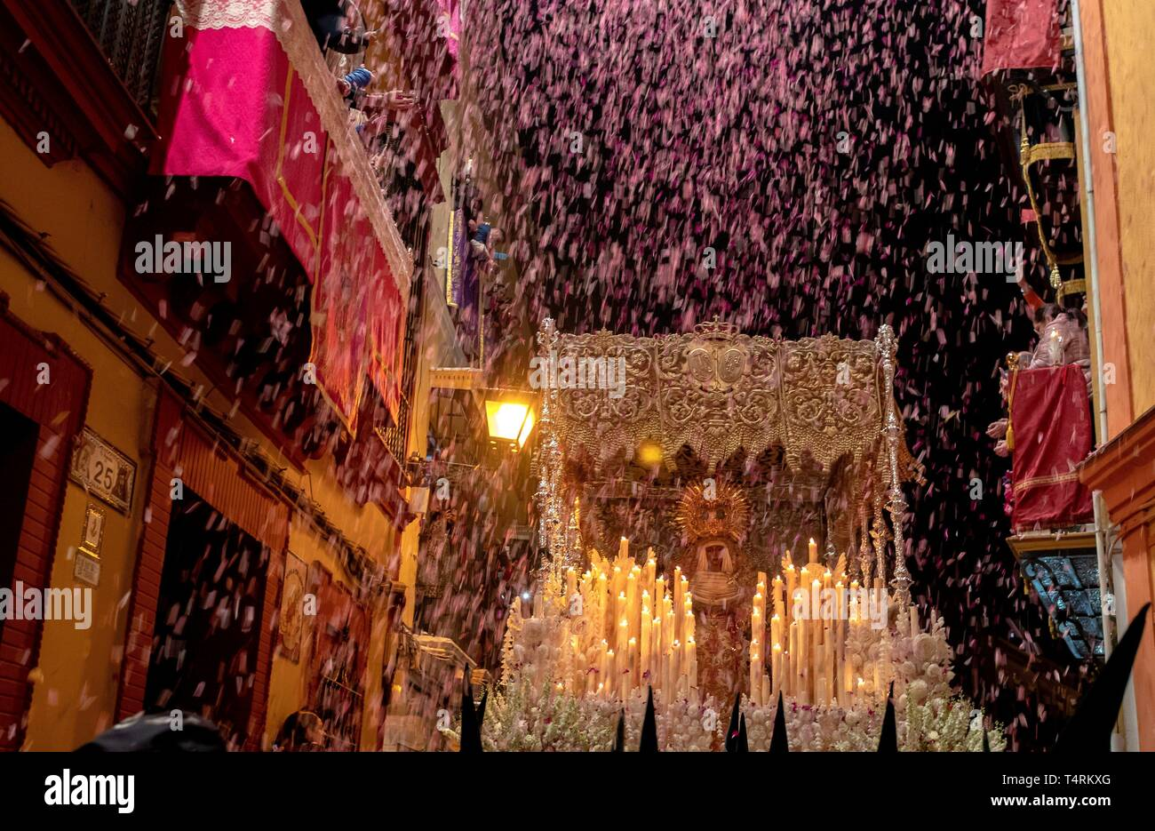 Petals are thrown from the balconies as the Virgin of Esperanza de Triana leaves its temple at the neighborhood of Triana during the 'Madruga' (lit: Small Hours) processions in Seville, Spain, 19 April 2019. EFE/ Julio Munoz - Stock Image