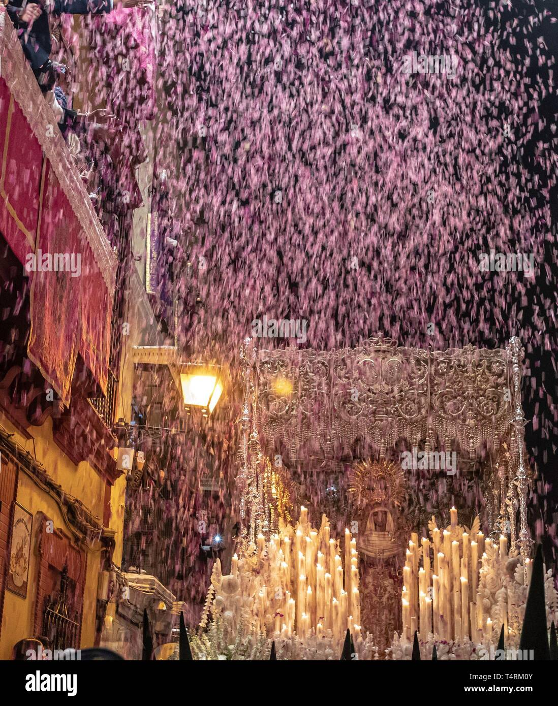 Seville, Spain. 19th Apr, 2019. Petals are thrown from the balconies as the Virgin of Esperanza de Triana leaves its temple at the neighborhood of Triana during the 'Madruga' (lit: Small Hours) processions in Seville, Spain, 19 April 2019. EFE/ Julio Munoz Credit: EFE News Agency/Alamy Live News - Stock Image