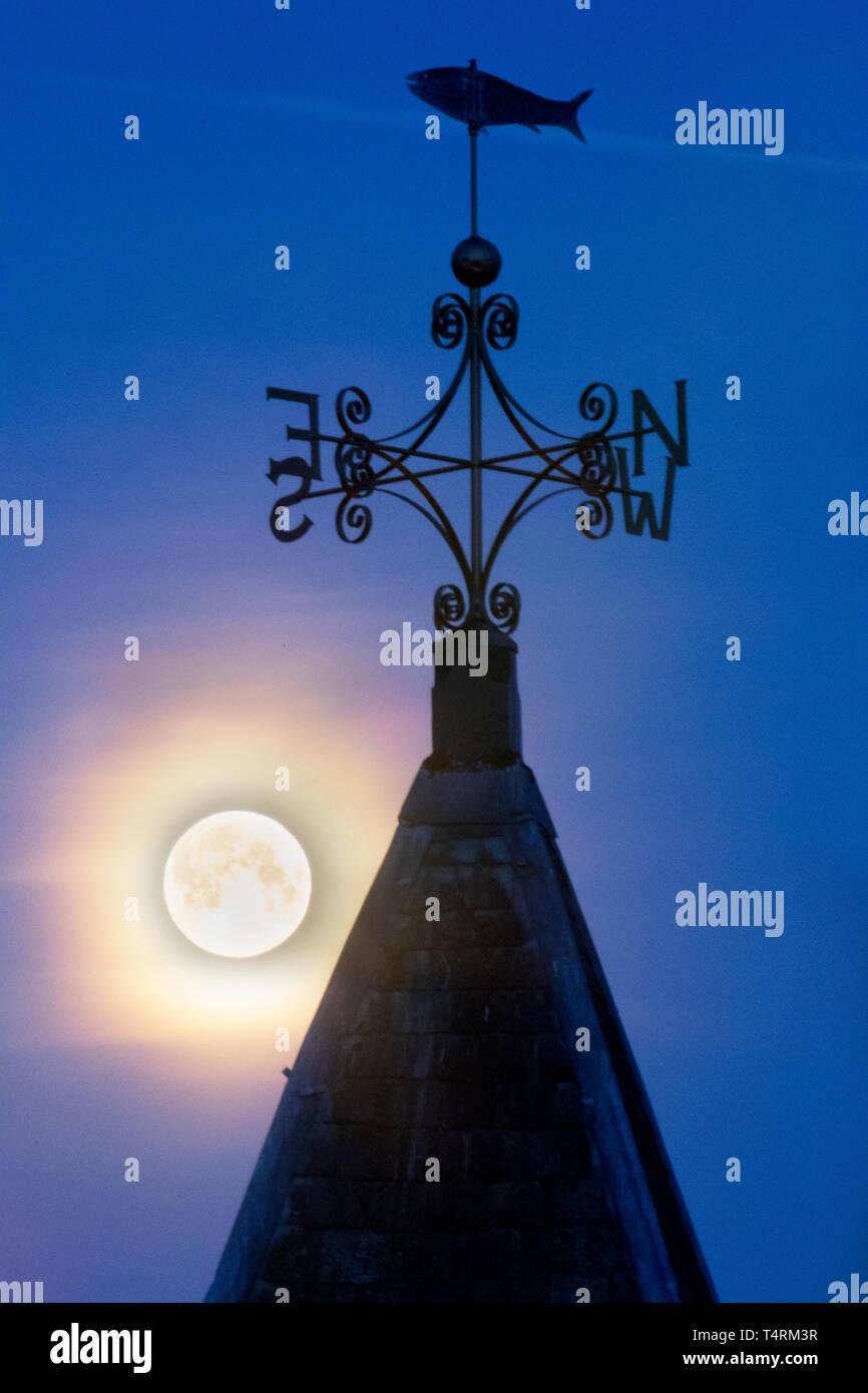 Fylde Coast, Lancashire. 19th April, 2019. UK Weather.  Clear skies at moonrise, with moonshine highlighting the seaside weathervane over the lifeboat station in Blackpool. Credit: MediaWorldImages/AlamyLiveNews. - Stock Image