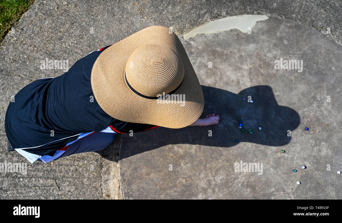 Crawley Sussex, UK. 19th Apr, 2019. Donna Davies from the Swansea Bay Snipers wears a large sun hat at the World Marbles Championship held at The Greyhound pub at Tinsley Green near Crawley in Sussex . The annual event has been held on Good Friday every year since the 1930s and is open to players from around the world Credit: Simon Dack/Alamy Live News Stock Photo