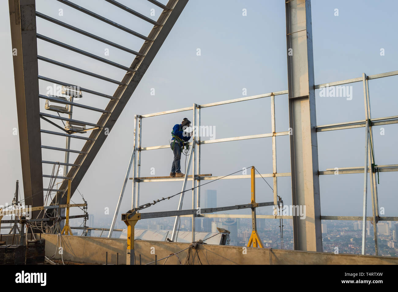 Asian worker weld on top of high building without scaffolding, low safety working condition - Stock Image