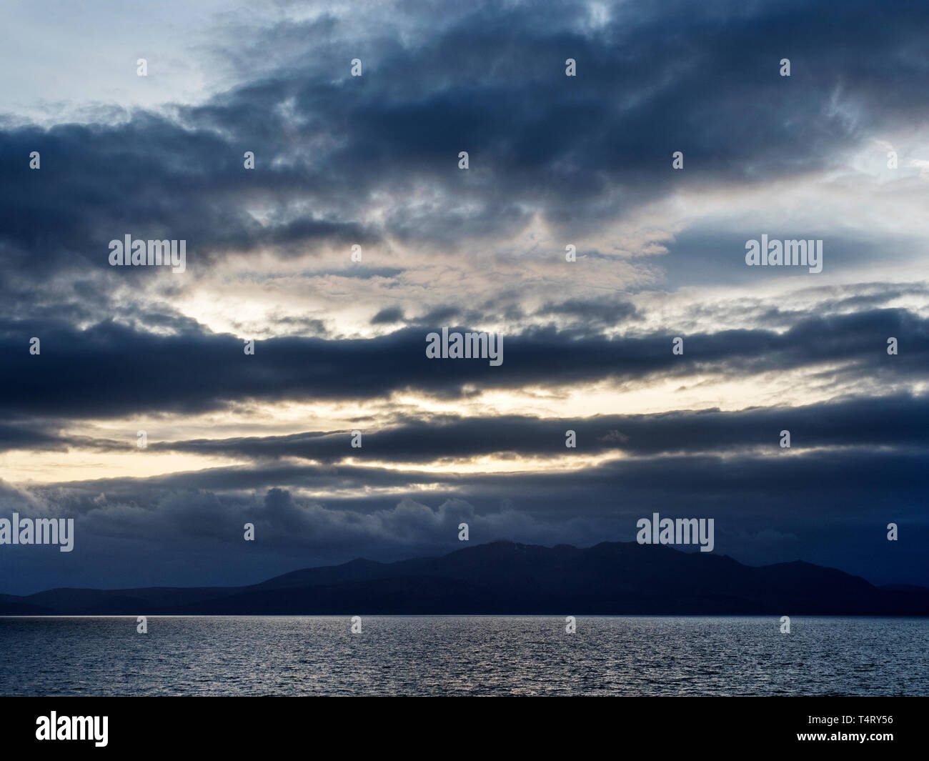 Dark clouds over the Isle of Arran at dusk North Ayrshire Scotland - Stock Image