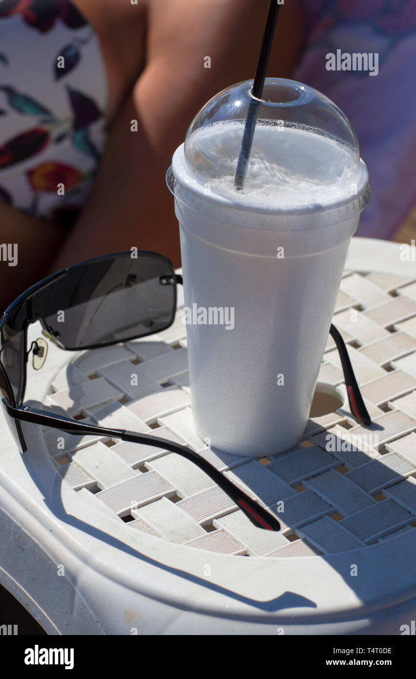 Greek coffee frappe in cup with foam near sunglasses on blurred background body part of woman with bra - Stock Image