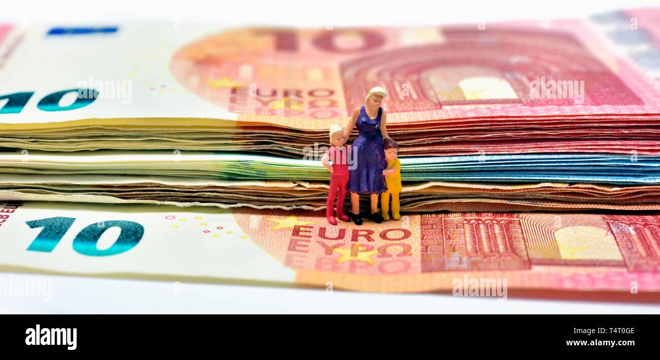 Miniature figurines,single parent with children, sitting on euro notes,currency, - Stock Image