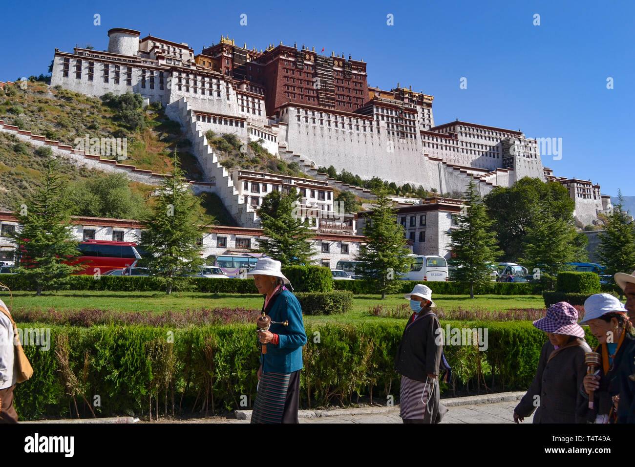 Pilgrims of Tibetan Buddhism walking in front of Potala Palace in Lhasa, Tibet - Stock Image