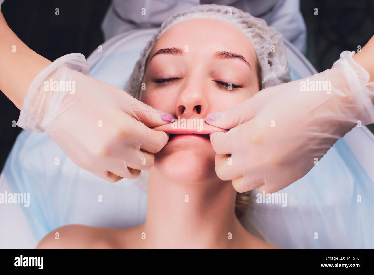 cosmetologist makes a buccal massage of the patient's facial muscles - Stock Image