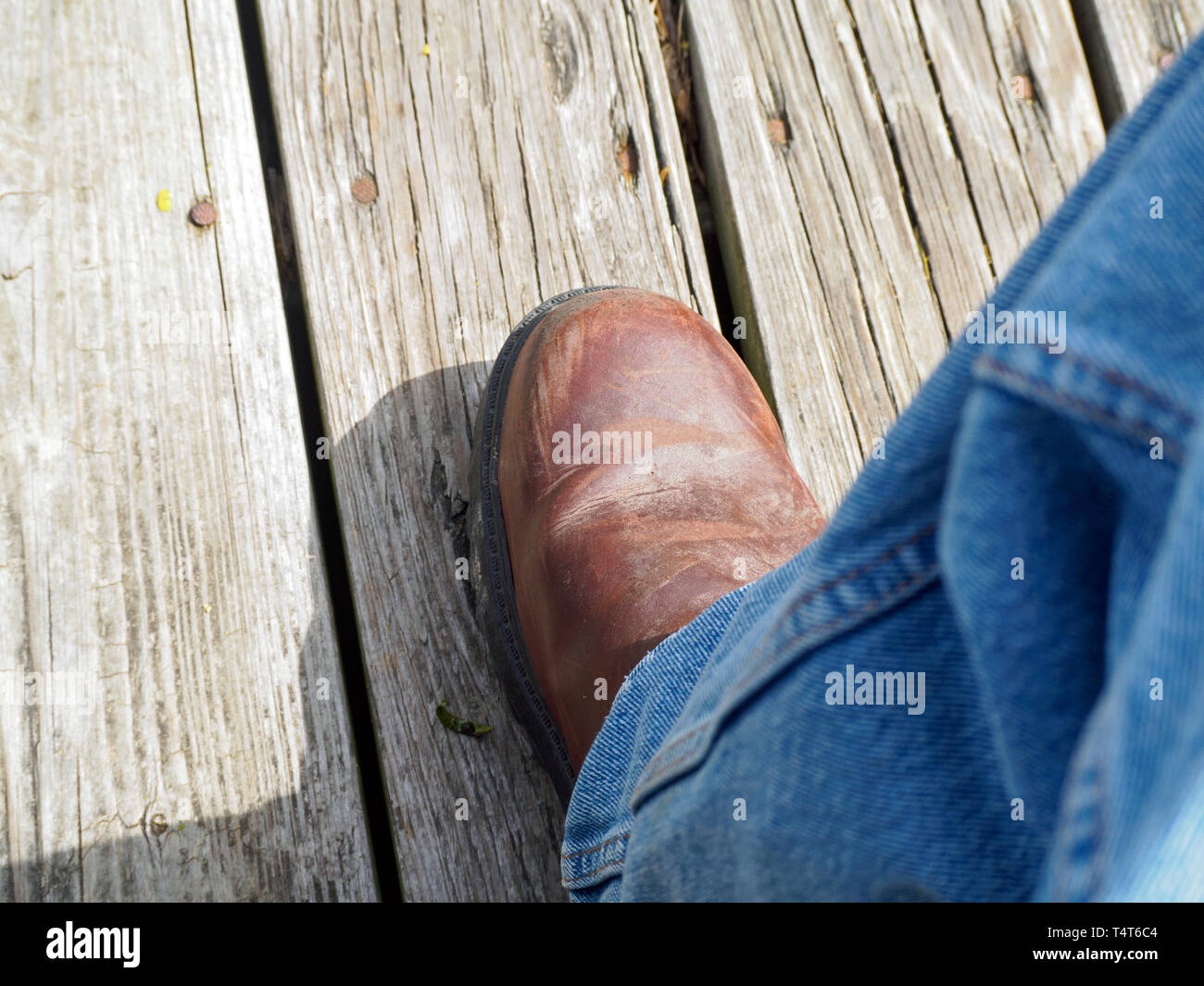 A scuffed brown leather boot with blue jeans on weathered wooden deck, view from above - Stock Image