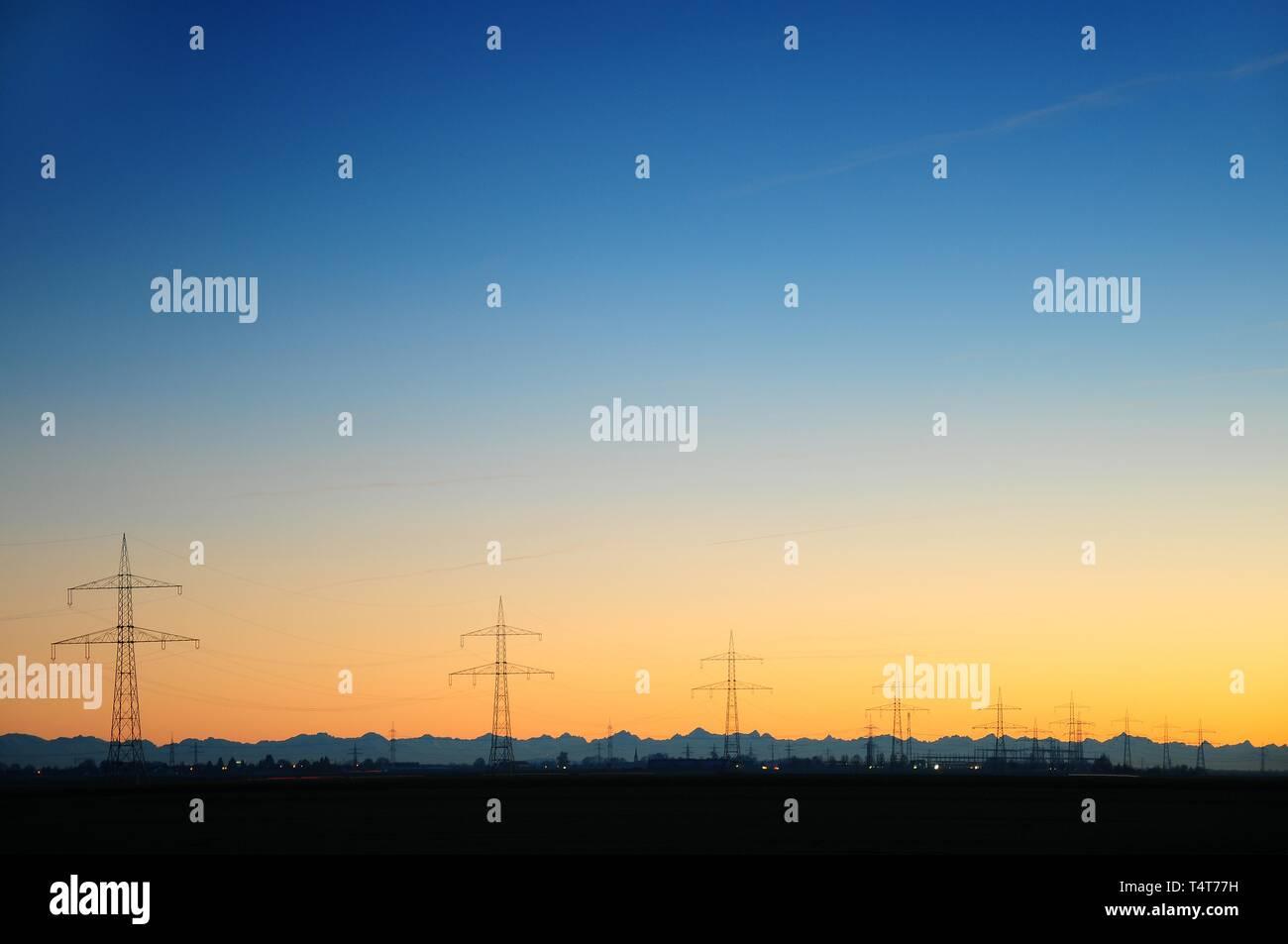Sunset, powerlines, Alps in Lechfeld in Bobingen, Swabia, Bavaria, Germany, Europe - Stock Image
