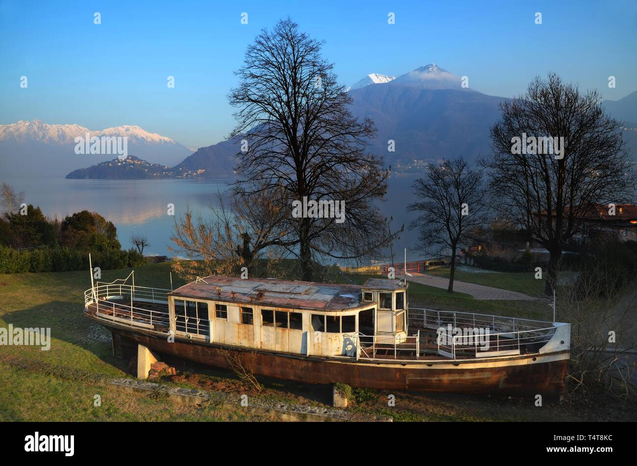 Old passenger ship on the field and trees with branches and alpine lake with snow-capped mountain in Lombardy, Italy. - Stock Image