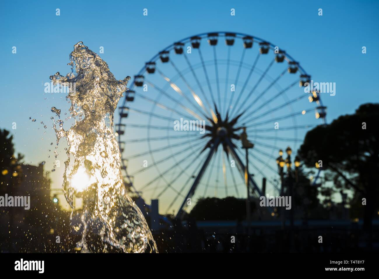 Water Fountain and Ferris Wheel with Sunset in Nice, France Stock Photo