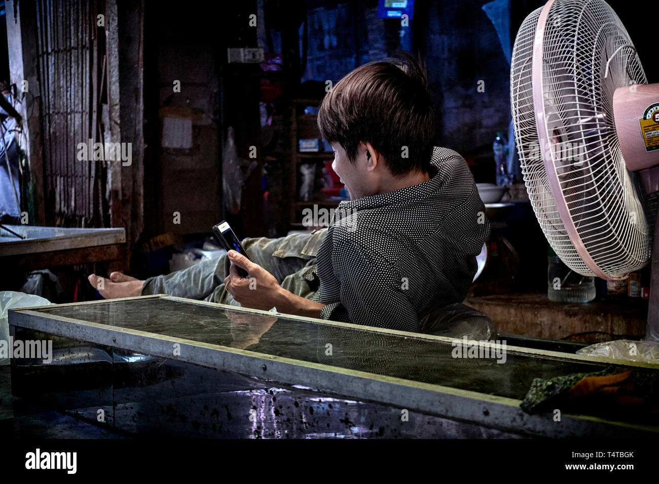 Thailand. A very hot day and a man cooling off in front of a cooling fan - Stock Image