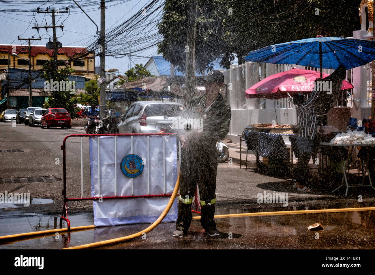 Songkran Thailand New Year and water festival 2019 with hosepipe used to spray water over passing motorists - Stock Image