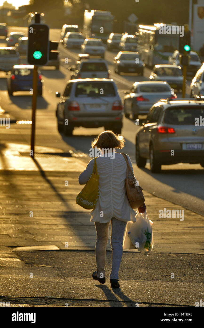 A portrait view of a woman with shopping bags, walking along the footpath of a busy street, backlit by sunset. Western Australia. - Stock Image