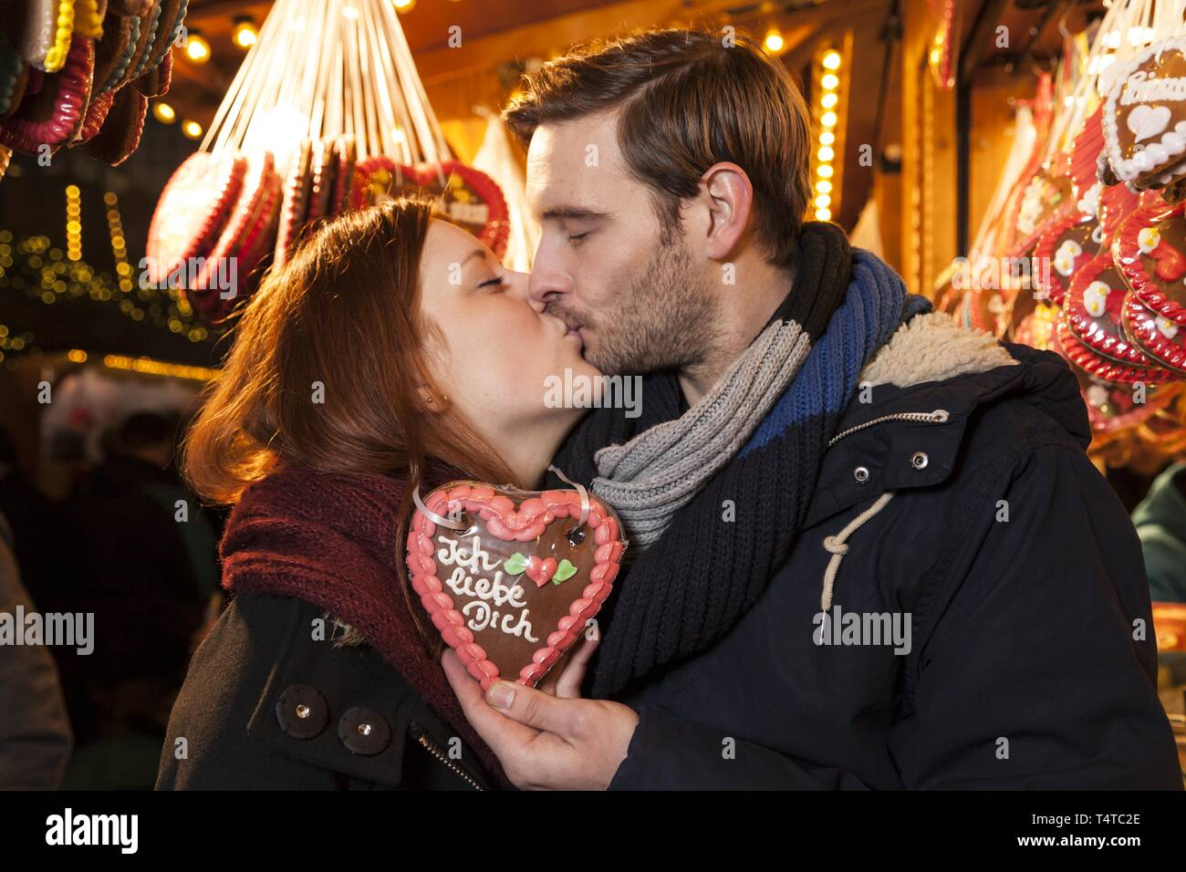 A couple kissing on a Christmas market, gingerbread heart with saying 'Ich liebe Dich', Germany, Europe - Stock Image