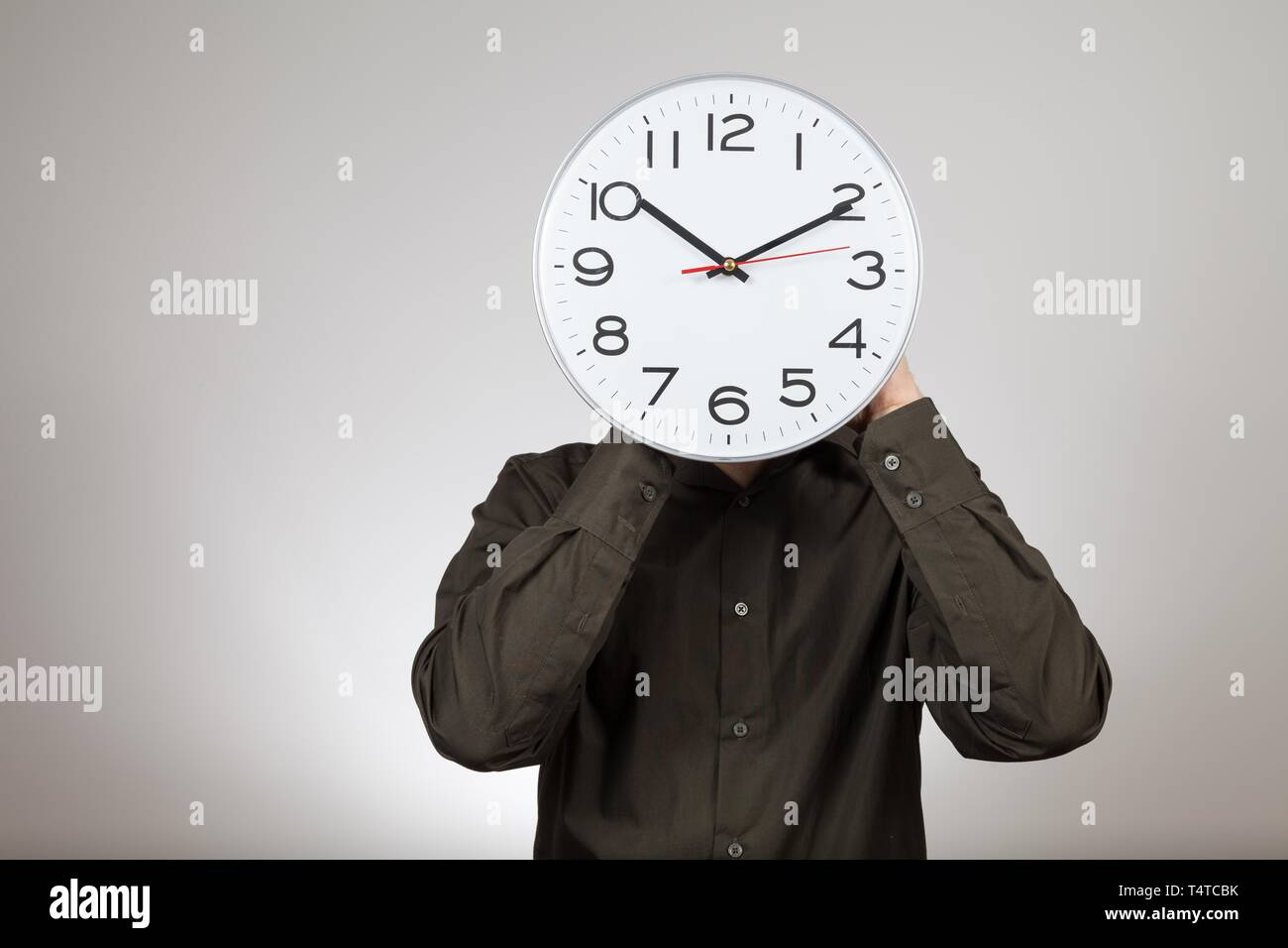 Symbolic image working hours, man holding a clock in front of his face - Stock Image