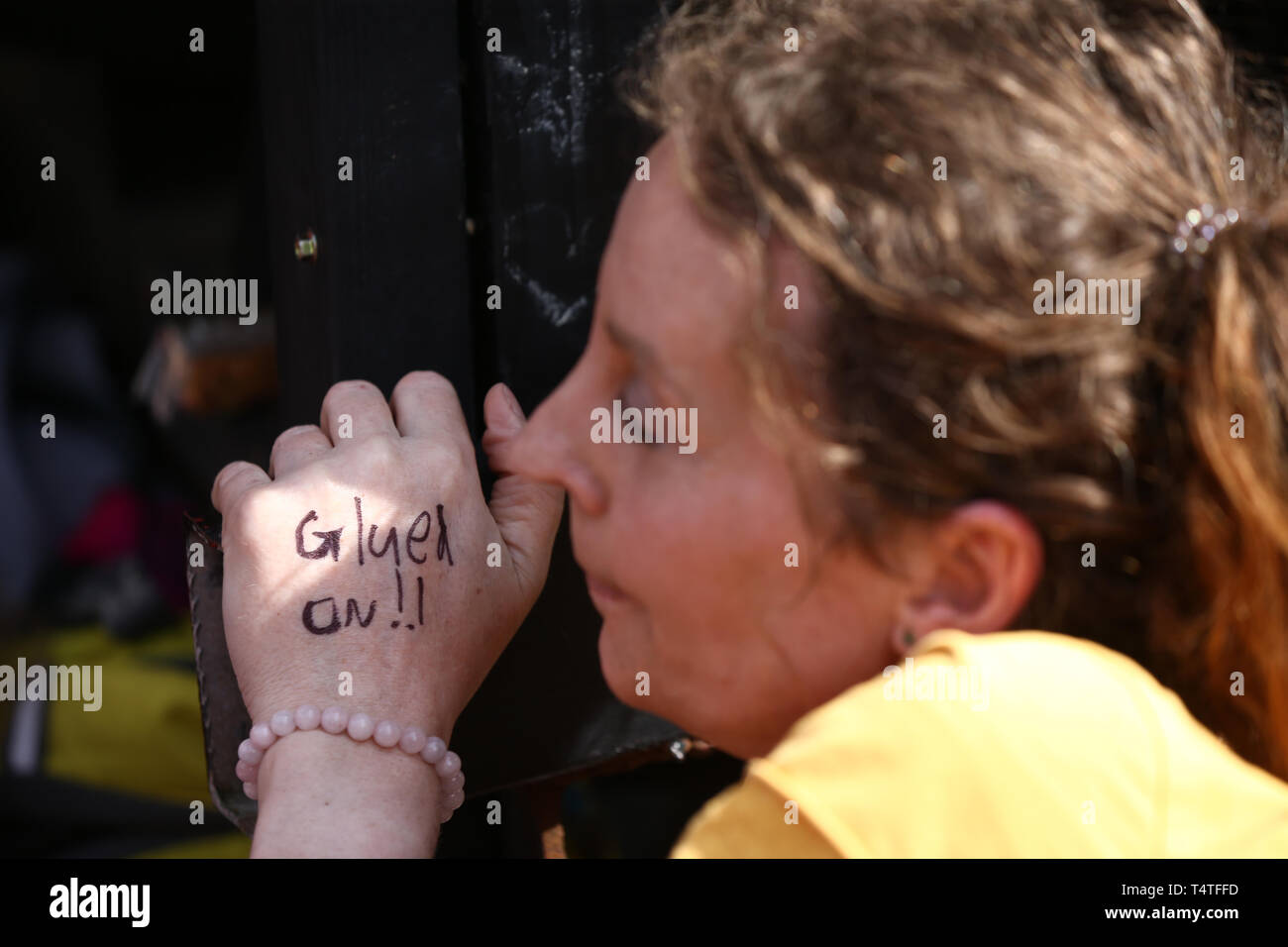 A climate activist with a warning note written on her hand during an Extinction Rebellion demonstration at Oxford Circus, London. Londoners face a fourth day of disruption in the capital, despite nearly 400 arrests. - Stock Image
