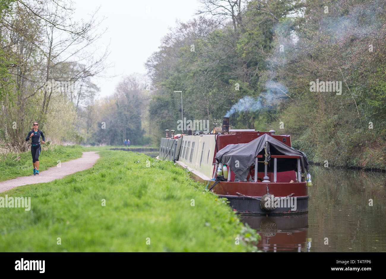 Landscape shot of narrowboat with smoking chimney moored alongside UK canal with female runner (front view) jogging along canal towpath. - Stock Image