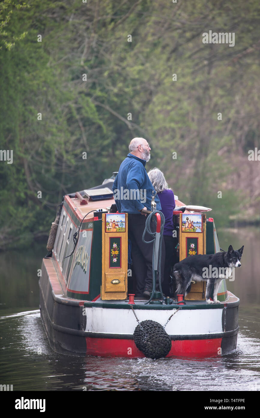 Close up of middle-aged couple with pet dog away from home, travelling the British waterways, enjoying their leisure time on a narrowboat on UK canal. - Stock Image