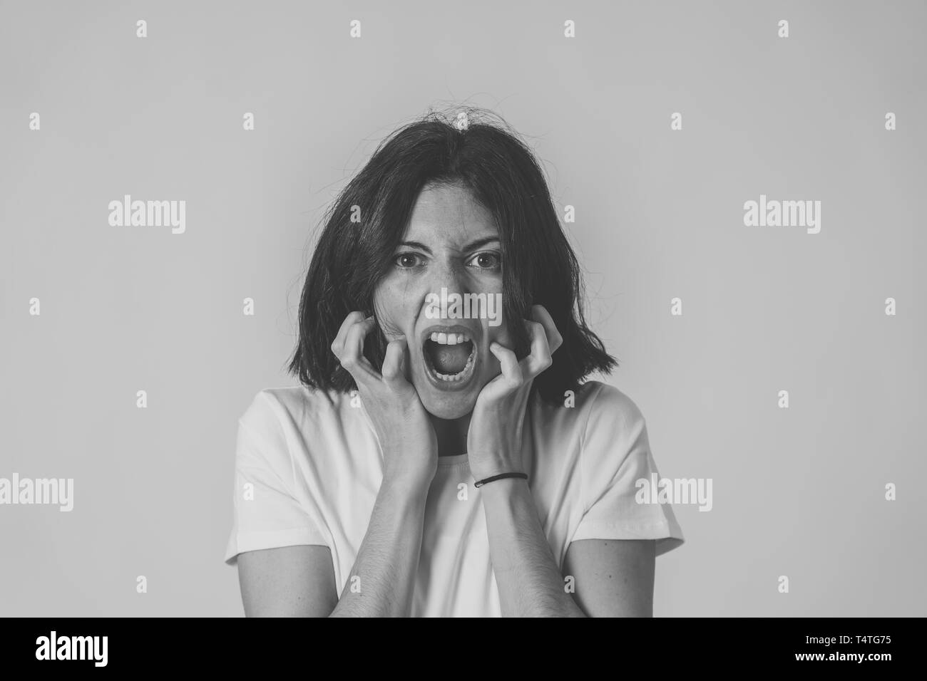 Black and white close up of young frustrated caucasian woman with angry and stressed face. Looking mad and crazy shouting and making hands gestures. C - Stock Image