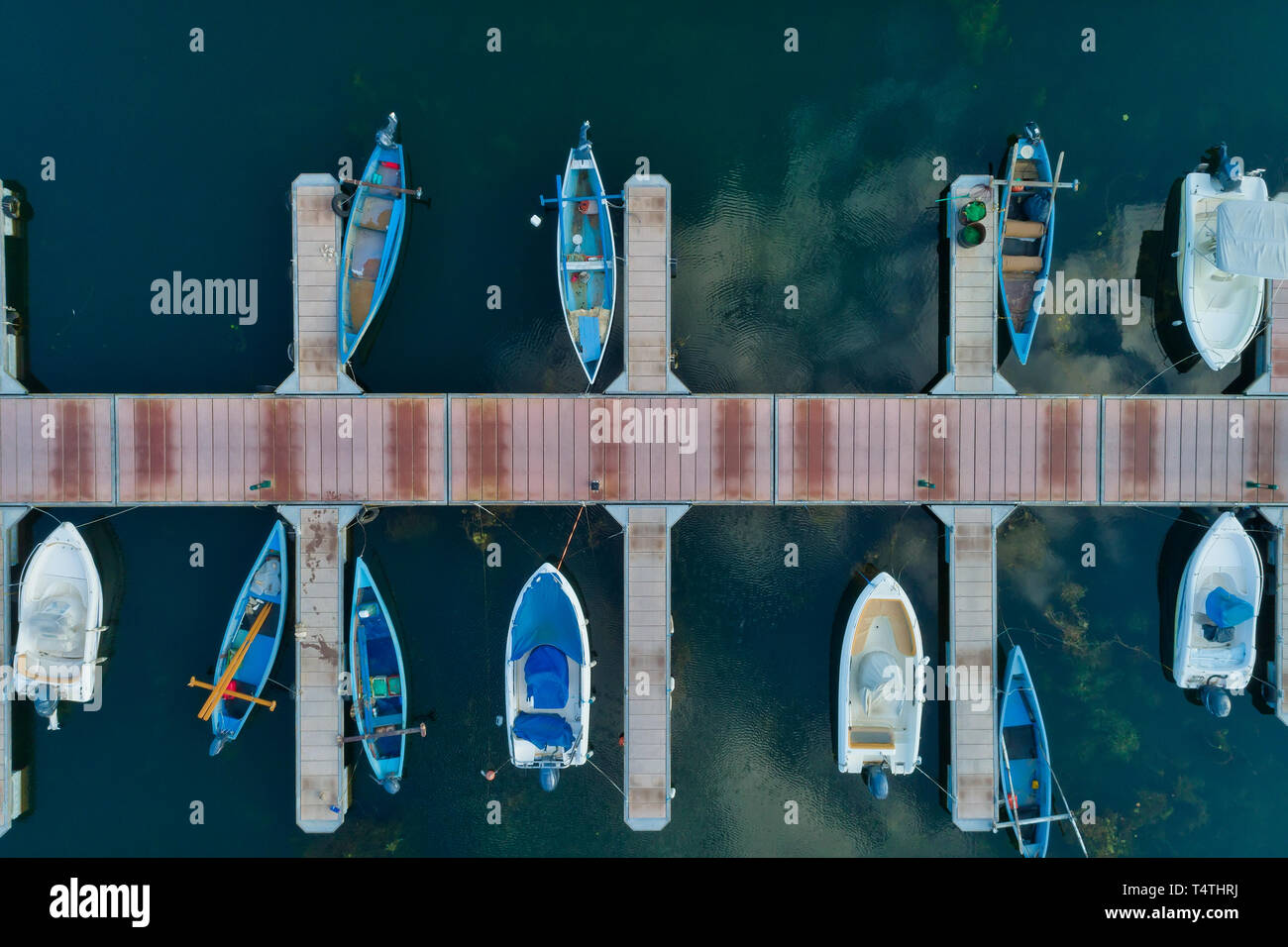 Aerial picture of floating dock with boats, motorboats and vessels floating on water in lake Small Prespes, Northern Greece Stock Photo
