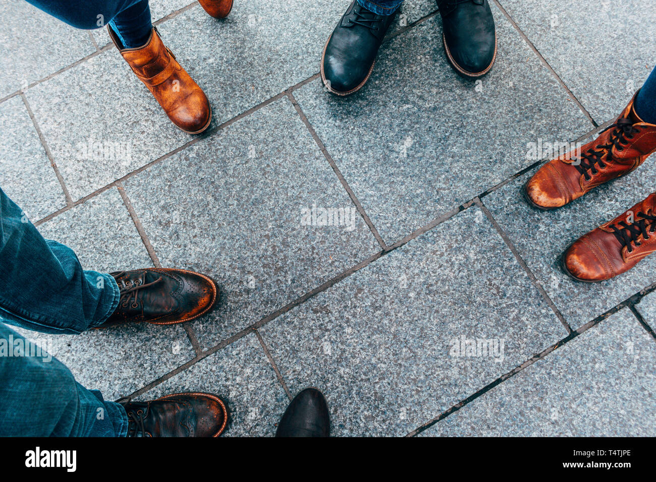 Worn out shoes on sidewalk - Stock Image