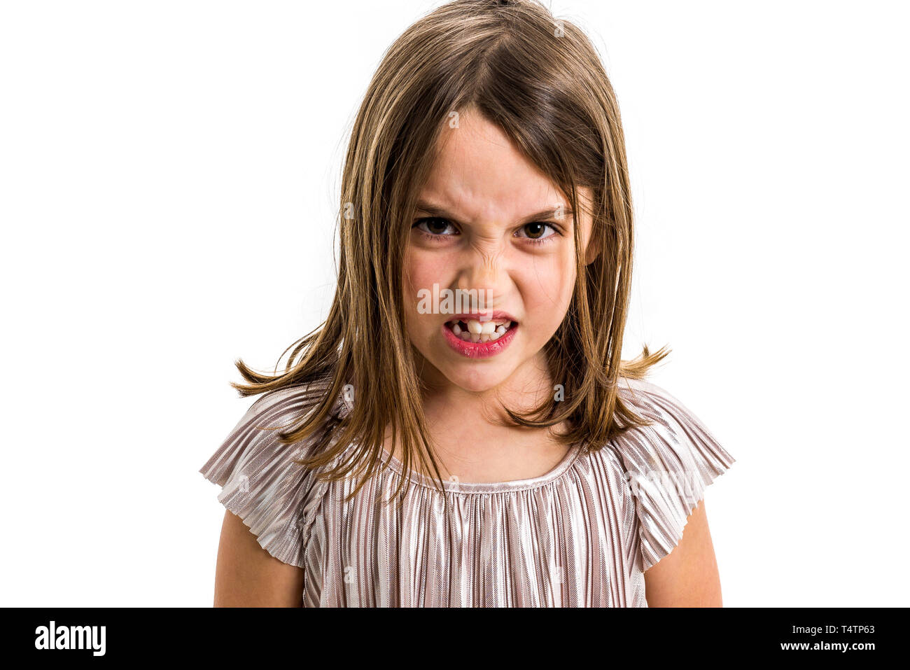 Little young girl is angry, mad, disobedient with bad behaviour. Children making the act of insubordination and disobedience, yelling, showing teeth,  - Stock Image