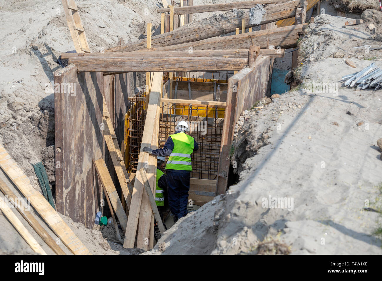 Deep trench shoring to avoid risks of landslide. Walls with supports to prevent sloughing of the soil. Trenching and excavation safety. - Stock Image