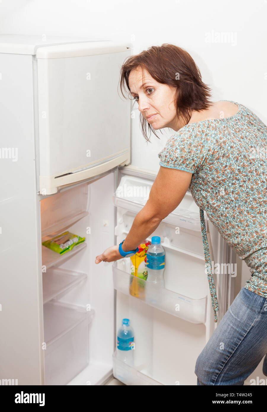 A woman shows with her hand in an empty fridge - Stock Image