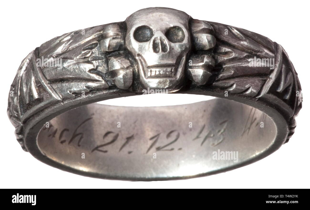 """A SS deathïs head ring, custom-made by the jeweller Gahr in Munich, soldered underneath the separately applied deathïs head, the inside surface with engraved dedication """"S.lb. Schützbach 21.12.43 H. Himmler"""". Weight 12.8 grammes, inside diameter 21 mm. historic, historical, 20th century, 1930s, 1940s, Waffen-SS, armed division of the SS, armed service, armed services, NS, National Socialism, Nazism, Third Reich, German Reich, Germany, military, militaria, utensil, piece of equipment, utensils, object, objects, stills, clipping, clippings, cut out, cut-out, cut-outs, fascism, Editorial-Use-Only Stock Photo"""