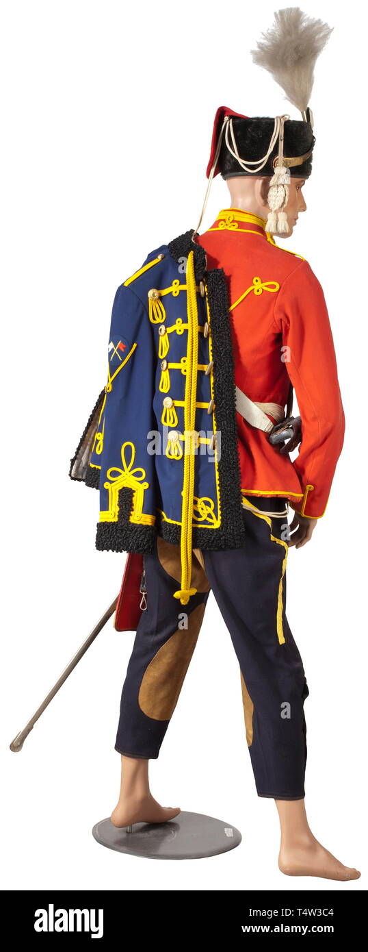 The complete estate of uniforms of a Gefreiter of the 3rd Squadron of the Leibhusaren-Regiment. A red attila with yellow cording and guard's lace. Dark-blue trousers with sewed-on yellow lace and riding leather trimming. A red 'Krätzchen' (field cap) with blue edging and yellow piping (multiple issue stampings and name label of the Gefreiter (Private) Silbersiepe.) A blue faux fur attila with yellow cording, on the sleeve the Signaler's Badge and the decoration for proficiency with the lance. A busby for enlisted men with guard's star, field insi, Additional-Rights-Clearance-Info-Not-Available - Stock Image