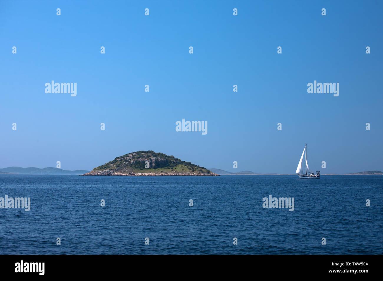 Cruising yacht passing Mali Tetovišnjak in the Murtersko more (Murter Sea), Croatia - Stock Image