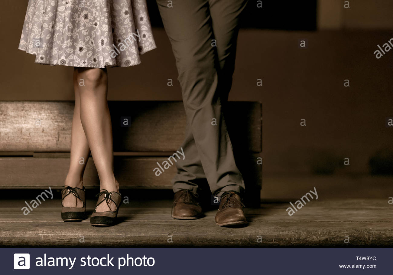 Crossed legs of a couple standing on a wooden bench. - Stock Image